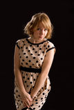 Demure young woman in a polka dot dress. Beautiful blonde demure young woman in a polka dot dress posing with her hands clasped in front of her against a dark Stock Photos