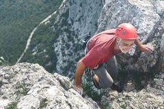 denåldrades mannen vaggar klättrareklättringar på klippan Royaltyfria Bilder