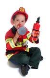 Denår pojken i brandmandräkt Arkivbild