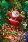 Denår toyen av Santa Claus hängningar på en jultree Royaltyfri Foto
