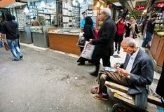 Den äldre allvarliga arbetaren av den orientaliska marknaden tjänade några pengar och räknar räkningarna Royaltyfri Foto