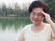 Den äldre asiatiska kvinnan bar exponeringsglas hon var inte bekväm med huvudvärker När hög kvinna som går i parkera royaltyfria foton