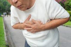 Den äldre asiatiska kvinnan med bröstkorgen smärtar med hjärtinfarkt på allmänheten parkerar fotografering för bildbyråer