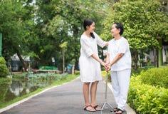 Den äldre asiatiska kvinnan som går för att göra fysiskt med pinnen på, parkerar, tar dottern omsorg och service royaltyfri foto