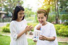 Den äldre asiatiska modern som använder incitamentspirometeren, eller tre bollar för stimulerar lungor, tar uppmuntrandottern oms royaltyfria bilder