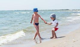 Den äldre brodern spelar på stranden med hans yngre bror, vågor, lyckliga barn royaltyfri foto