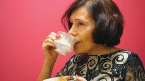 Den äldre brunettkvinnan dricker en kopp te och äter godisen på röd bakgrund arkivfilmer