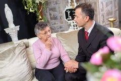 Den äldre damen i kapell vilar med den anpassade unga mannen arkivbilder