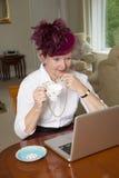 Den äldre damen som bär en hatt med, skyler genom att använda bärbara datorn Royaltyfri Bild