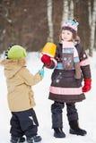 Den äldre flickan ger eskimo till mer ung barn i vinter parkerar Arkivbild