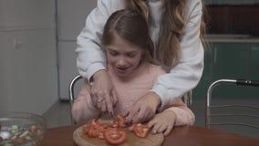 Den äldre flickan undervisar mer ung flicka att klippa tomater för sallad Två systrar som reser upp grönsaksallad, medan sitta på arkivfilmer