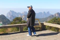 Den äldre fotvandraren tycker om panoraman i de Huangshan gulingbergen fotografering för bildbyråer