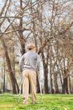 Den äldre gentlemannen med kryckor som in går, parkerar Arkivfoto