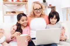 Den äldre härliga kvinnan ser bärbara datorn som skrattar med hennes lilla barnbarn arkivbild