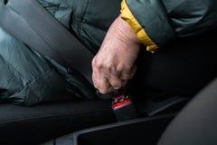 Den äldre höga kvinnan fäster en säkerhetsbälte i en bil som bär det gröna och gula omslaget arkivfoto