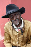 Den äldre haitira gentlemannen i hatt poserar i lantlig by Arkivbilder