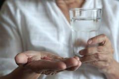den äldre kvinnan äter medicin och med preventivpillerar och exponeringsglas av w arkivbild