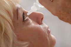 Den äldre kvinnan behandlar henne ögon med läkarbehandlingen Arkivbild