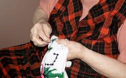 Den äldre kvinnan broderar trådar Fotografering för Bildbyråer
