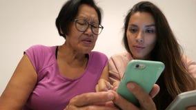 Den äldre kvinnan för det blandade loppet lär hur man använder mobiltelefonen Pensionerad moder och barndotter som använder moder lager videofilmer