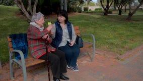 Den äldre kvinnan frågar för en drink, medan strosa med volontären stock video