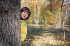 Den äldre kvinnan går i höstskog Arkivfoton