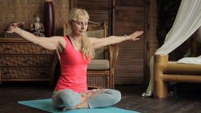 Den äldre kvinnan gör sofistikerade yogaövningar på Buddhastatybakgrund stock video