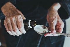 Den äldre kvinnan häller medicin i sked för att ta läkarbehandlingen, hälsovård av begreppet för äldre folk Arkivbild