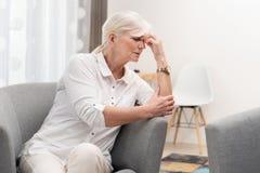 Den äldre kvinnan har en huvudvärk royaltyfria foton