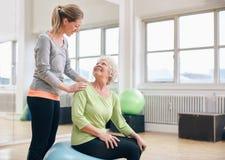 Den äldre kvinnan hjälpte vid den personliga instruktören på idrottshallen Arkivbilder