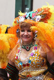 Den äldre kvinnan i gula fjädrar som marscherar i karneval, ståtar, Peru Royaltyfria Foton