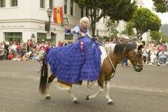 Den äldre kvinnan i lilor klär och att rida varje år efter 1924, ritter igen i 2006 på invigningsdag på den gamla spanska dagfies Royaltyfri Foto