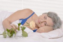 Den äldre kvinnan i säng med steg Royaltyfri Bild