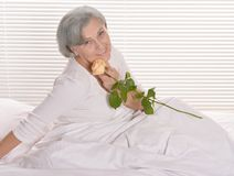 Den äldre kvinnan i säng med steg Fotografering för Bildbyråer