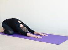 Den äldre kvinnan i yogabarn poserar Arkivfoto