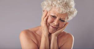 Den äldre kvinnan kommer med tillbaka minnen av barnåldern arkivfoton