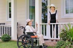 Den äldre kvinnan kopplar av i trädgård med dottern Royaltyfri Foto
