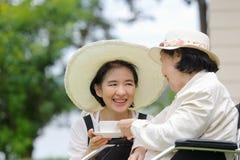 Den äldre kvinnan kopplar av i trädgård med dottern Arkivbild