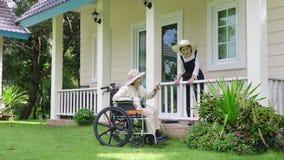 Den äldre kvinnan kopplar av i trädgård med dottern arkivfilmer