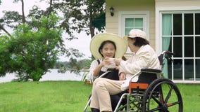 Den äldre kvinnan kopplar av i trädgård med dottern stock video