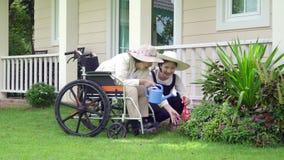 Den äldre kvinnan kopplar av i trädgård med dottern lager videofilmer