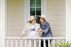 Den äldre kvinnan kopplar av i trädgård med dottern Royaltyfria Bilder