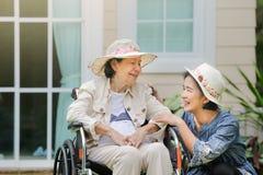 Den äldre kvinnan kopplar av i trädgård med dottern Royaltyfria Foton