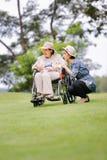 Den äldre kvinnan kopplar av i trädgård med dottern Arkivbilder