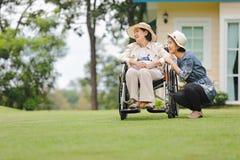 Den äldre kvinnan kopplar av i trädgård med dottern Arkivfoto