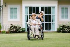 Den äldre kvinnan kopplar av på rullstolen i trädgård Royaltyfri Bild