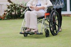 Den äldre kvinnan kopplar av på rullstolen i trädgård Arkivfoto