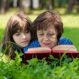Den äldre kvinnan och flickan ligger på gräsmattan, omfamnar och läser en bok mot grön naturbakgrund Arkivbilder