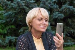 Den äldre kvinnan pratar vid den videopd budbäraren på mobiltelefonen Arkivfoton