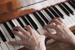 Den äldre kvinnan räcker att spela upp pianot, slut arkivbilder